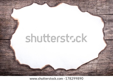 burnt paper on wood, can be used as a background or a frame for text - stock photo