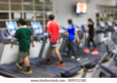 Burred people are jogging in fitness center - stock photo