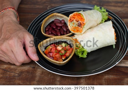 Burrito on ceramic ware, the Man eats a burrito, tasty, it is useful, vegetarian food