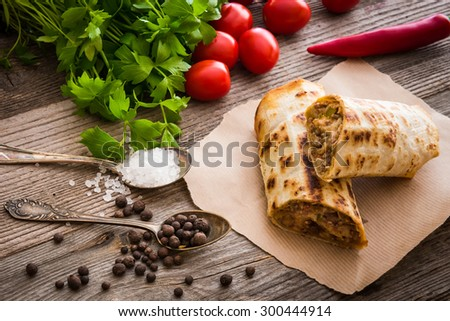burrito on parchment with vegetables and spices on a wooden background - stock photo