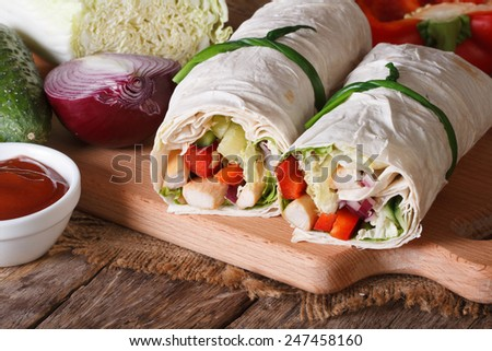 Burrito with chicken and vegetables close-up with the ingredients, horizontal  - stock photo