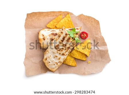 burrito with chips on parchment isolated on a white background - stock photo