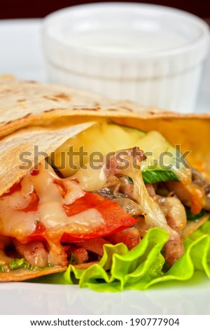 burrito with meat cheese and vegetables