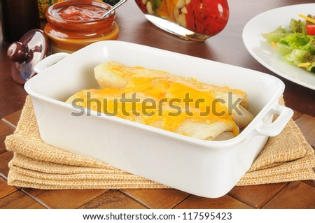 Burritos or chimichangas with melted cheese in a casserole dish