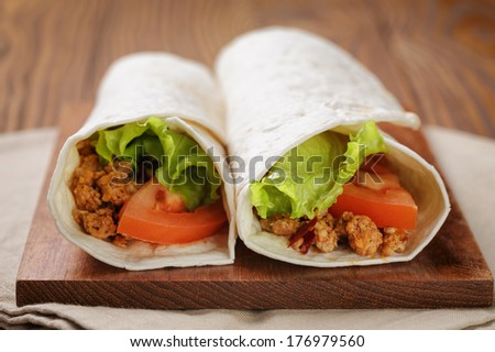 burritos with beef tomato and salad leaf on old wooden table rustic style