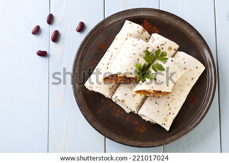 burritos wraps with meat beans and vegetables on blue wood board - stock photo