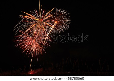 Burst of fireworks in night sky with copy space. - stock photo