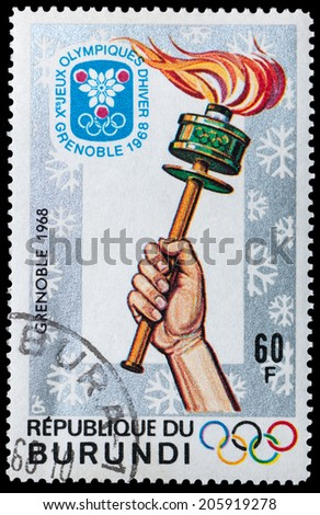 BURUNDI - CIRCA 1968: A post stamp printed BURUNDI, Olympic Winter Games - were held in Grenoble, France 1968, Games symbol - Hand with a torch, circa 1968 - stock photo