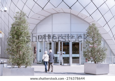 BURY ST EDMUNDS, UK - 21 APRIL 2015: shoppers walk past the main doors of the Debenhams department store in the Arc shopping complex.