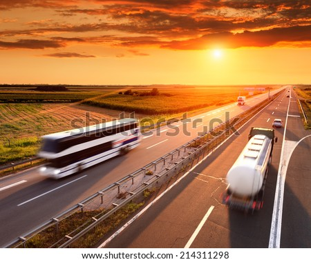 Bus and truck in motion blur on the highway at sunset  - stock photo