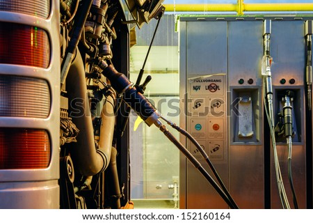 Bus at CNG, natural gas, station being filled with fuel,night shot - stock photo
