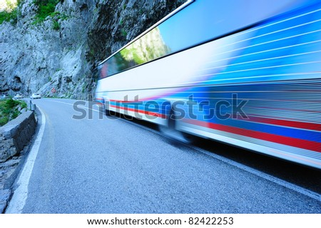 Bus moving along the mountain road - stock photo