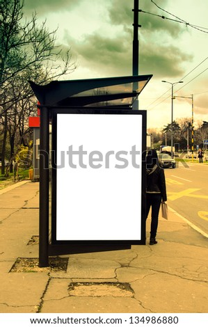 Bus station with blank poster on stormy day - stock photo
