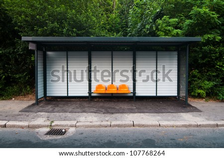 Bus station with orange plastic seats in the park - stock photo