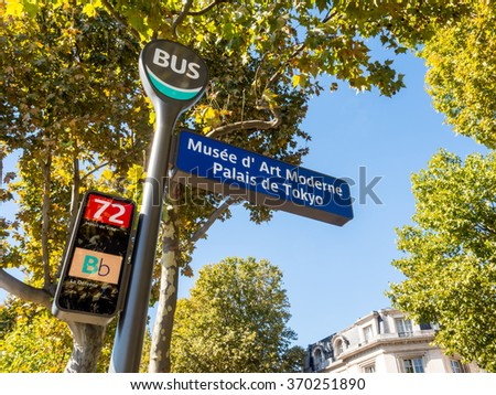 Bus stop in Pairs, France, under blue sky and green leaves tree in autumn