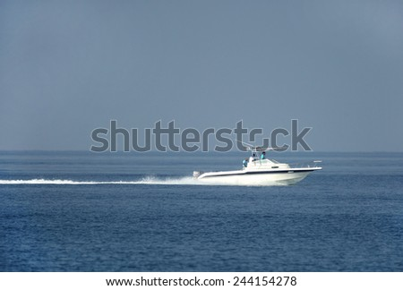 BUSAITEEN, BAHRAIN-SEPTEMBER 27: Early morning fisher men moving in the sea on speedboat at Busaiteen sea coast on September 27, 2014, Bahrain.  - stock photo