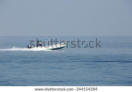 BUSAITEEN, BAHRAIN-SEPTEMBER 27: Early morning fisher men moving in the sea on speedboat at Busaiteen sea coast on September 27, 2014, Bahrain - stock photo