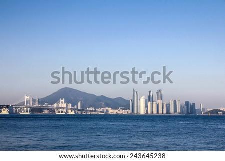 Busan city skyline with gwangan bridge from the sea - stock photo