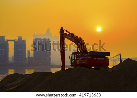 BUSAN, KOREA - April 2, 2016 : Sunrise and Excavator in Gwangan beach