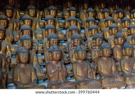 Busan South Korea, dozens of Buddhas inside the mountain Buddhist temple of Seokbulsa. - stock photo