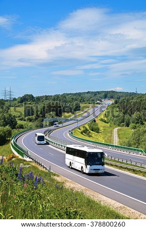 Buses on the highway with electronic toll gates in a countryside. The view from above. Sunny summer day with blue skies and white clouds. - stock photo