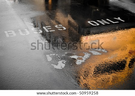 Buses Only Parking Spot Reflection to pick up children after rainy day - stock photo