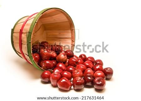 Bushel Basket Of Apples Spilling Out On White Background - stock photo