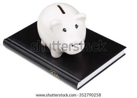 businees calendar and piggy bank over white background - stock photo