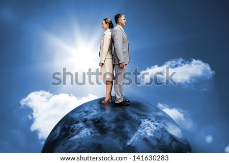 Busines people standing back to back on top of the world in blue sky with sun
