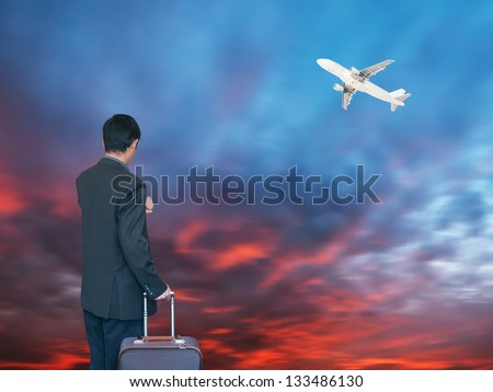 Busines person and plane on the background against cloudy sky - stock photo
