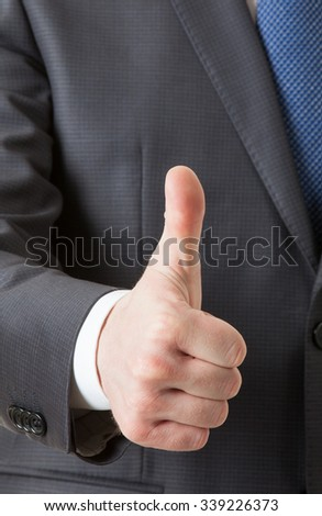 Businesman showing thumd up sign, white background
