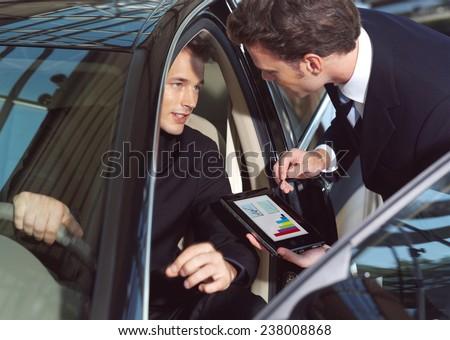businesmen working inside a car  - stock photo