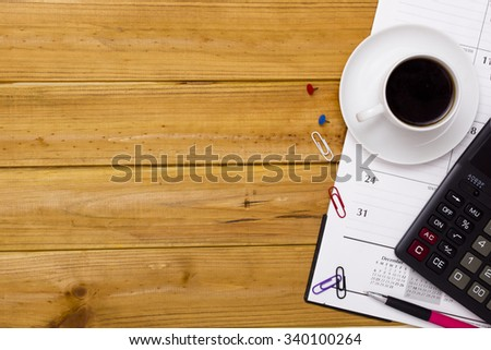 Business accessories - Calculator and office diary with cup of coffee on a wooden surface. - stock photo