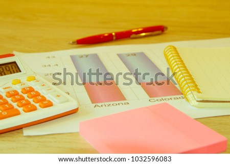 Business accessories ( notebook, calculator, fountain pen) and graphics, tables, charts on a wooden office desk. Sales earning chart
