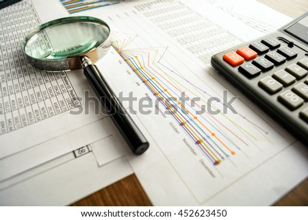 Business accessories (notebook, magnifier, calculator, planchette, tablet, fountain pen, notebook, glasses) and graphics, tables, charts on a wooden office desk. Soft focus