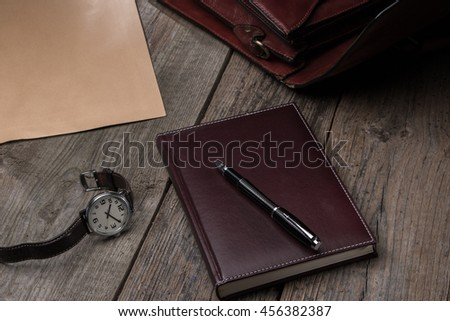 business accessories notebook, pen, rich portfolio, envelope, watch on wooden background