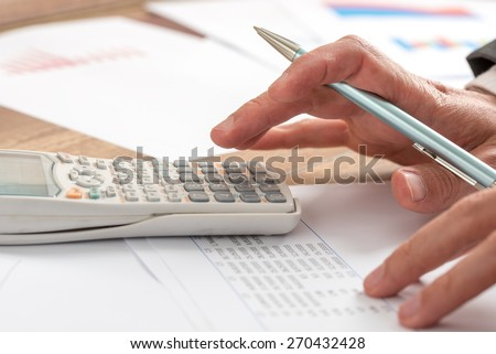 Business accountant doing a calculation on a manual desk top calculator, close up of his hand holding a pen. - stock photo