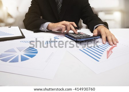Business accountant man working with calculator at a white paper chart in workplace.
