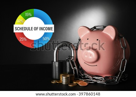 Business accounting concept. Piggy bank and chains on dark background - stock photo