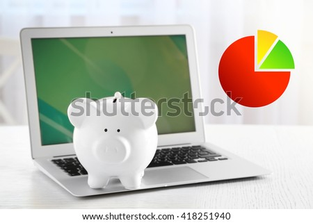 Business accounting concept.  Piggy bank with laptop on table indoors - stock photo