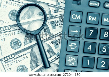 Business accounting or financial audit - Stack of dollar bills with a calculator and a magnifying glass - stock photo