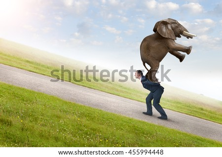 business adversity concept with businessman carrying elephant uphill - stock photo