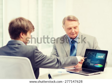 business, advertisement, technology and office concept - older man and young man with laptop computer in office - stock photo
