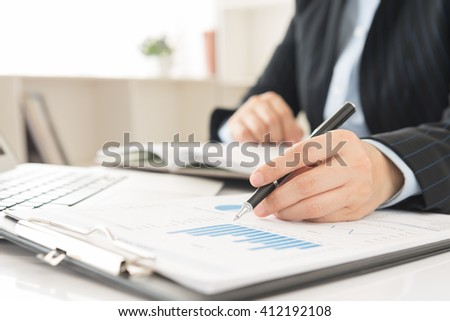 Business adviser analyze financial numbers to view the performance of the company. - stock photo