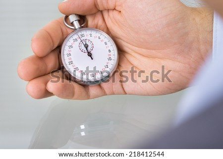 Business advisor holding stopwatch. Over the shoulder view - stock photo