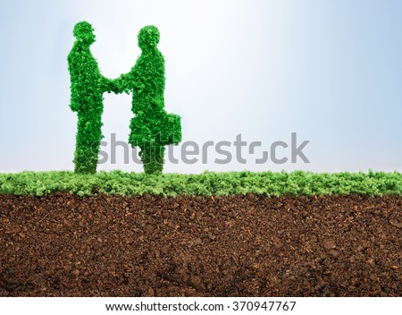 Business agreement concept with grass growing in shape of two businessmen shaking hangs