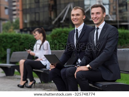 Business agreement. Two  confident motivated business partners are working on the project. Both  are wearing formal suits. Outdoor business concept. Their motivated colleagues are on the background