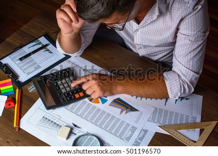 Business analysis - calculator, sheet, graphs (business report) and analyst hand, top view.