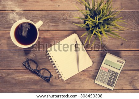 Business analysis concept. Top view workspace with booklet, pen, calculator, glasses and coffee mug. Wooden table background vintage toned. - stock photo