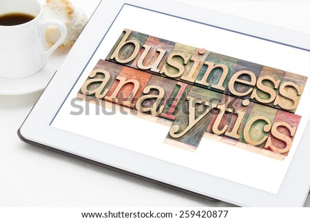 business analytics typography - text in letterpress wood type blocks on a digital tablet with a cup of coffee